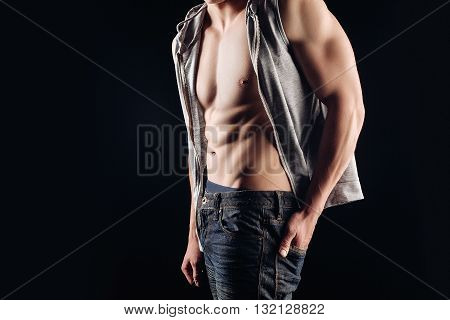 Close portrait of a naked torso. A man in a shirt undone, a denim outfit. Naked torso muscles cubes. Posing in the Studio. Black background