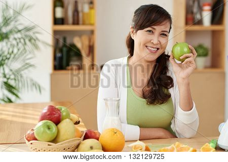 Portrait of cheerful mature Vietnamese woman holding green apple