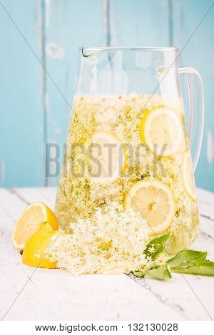 Elderflower and lemon slices in a jar for making elderflower syrup.