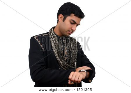 Indian In Traditional Clothes Looking At The Watch