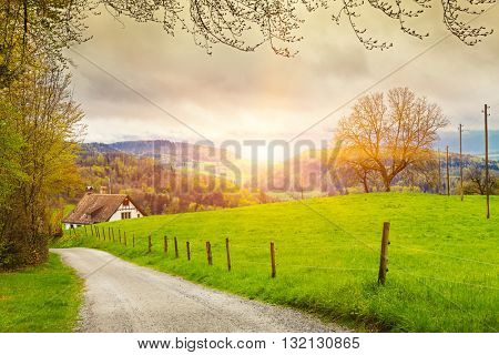 View of a spring day in the Switzerland, rural landscape at sunrise -  Switzerland rural sunset landscape. Countryside farm, green field, sun light and cloud. Europe.