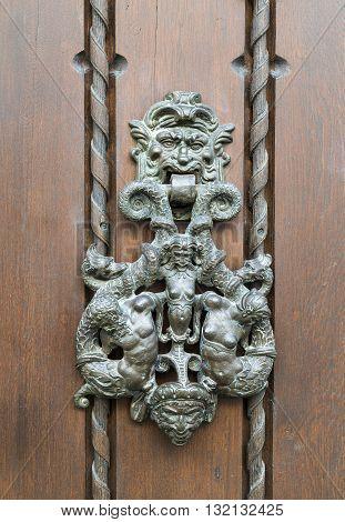 Knocker hammered metal door knocker on wooden door.