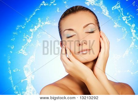 Beautiful young woman washing her face
