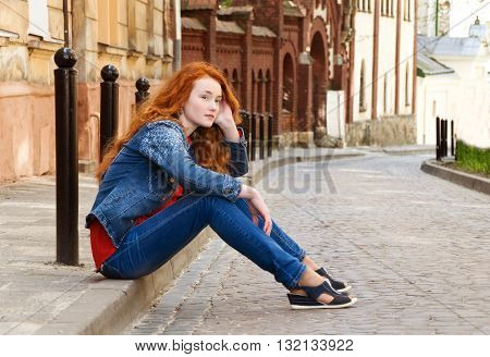 lonely girl tourist sits on the curb along the road