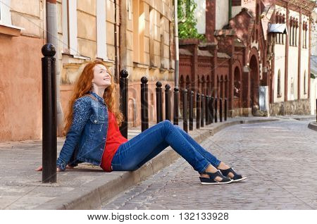 lonely girl tourist sits on the curb along the road and rest