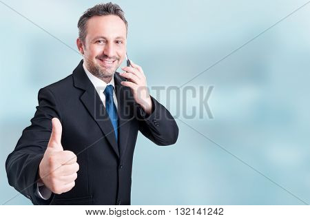 Trustworthy Handsome Manager Talking On Cellphone And Showing Thumbup