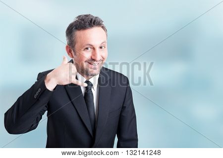Joyful Young Salesman Doing A Call Me Gesture With Hand