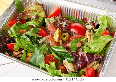 Healthy lunch. Natural organic food. Weight loss tasty diet, low carb food take away in aluminium boxes. Healthy food background. Vegetable seafood salad with mussel closeup at white wooden table