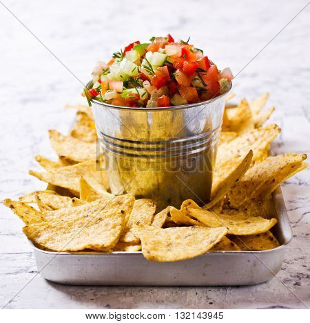 Fresh homemade salsa with vegetables and chips nachos. Selective focus.