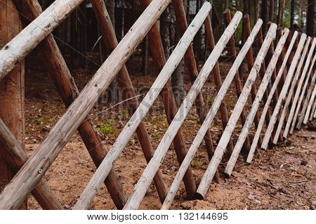 Beautiful wooden fence in the village. Daytime photo.