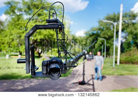 photocamera on the platform close-up and blurred videographer use camera crane in the park at summer day