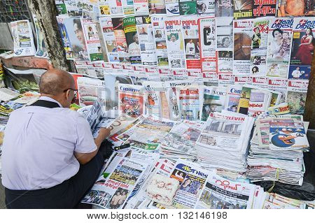 Yangon Myanmar - April 25 2016 : unidentifiled Burmese man reading Newpapaper at Newsstand on a street of Yangon