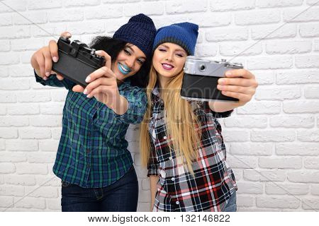 Two hipster girls taking photo with retro cameras over white wall.