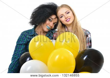 Two happy hipster girls have fun with balloons over white background