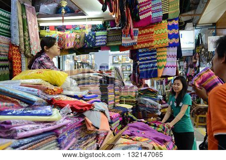Yangon Myanmar - April 26 2016 : People buying traditional burmese clothes in a clothes shop in Bogyoke market