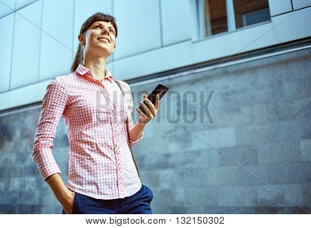 young woman with phone standing outdoor. Lifestyle or business concept