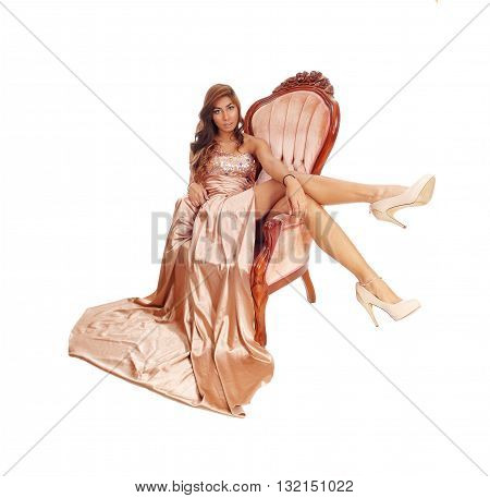 A lovely young woman in a gold color evening dress sitting in an armchair with her legs over the side isolated for white background.