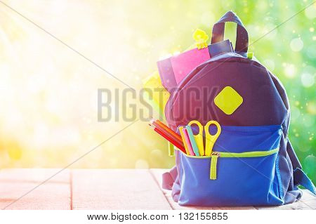 Full School backpack on wooden and nature background. Toning image.