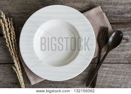 Empty dish with spoon and fork on old wooden background Top view