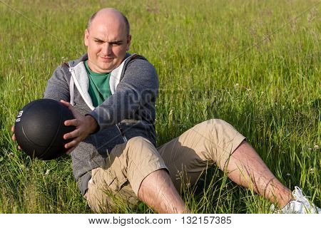 Man Trains With A 3 Kilogram Medicine Ball Sitting On The Gras