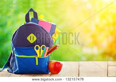 Full School backpack with apple on wooden and nature background