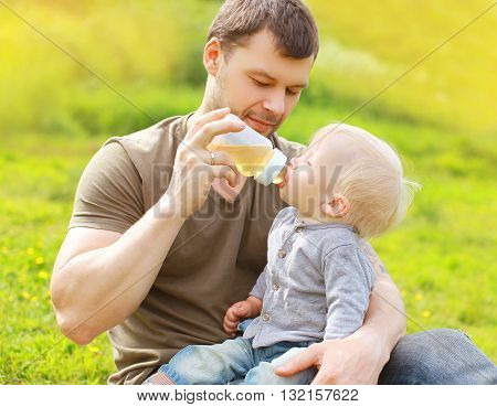 Father Feeds Baby From Bottle On Grass In Summer Day
