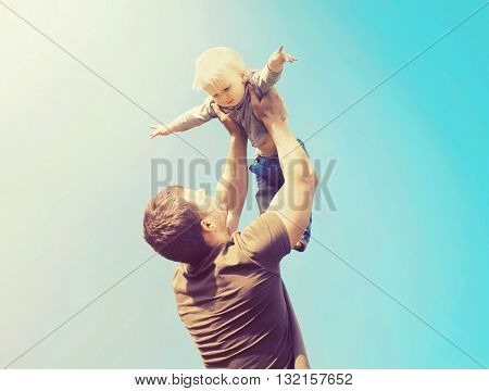 Happy Father And Son Playing Having Fun Together Outdoors Over Blue Sky