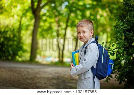 Cute little kid boy with books and backpack on green nature background. Back to school concept