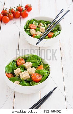 Vegan tofu salad with tomatoes and lamb's lettuce