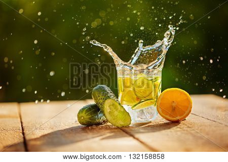 Detox water with lemon and cucumbers with splash on wooden table and green nature background