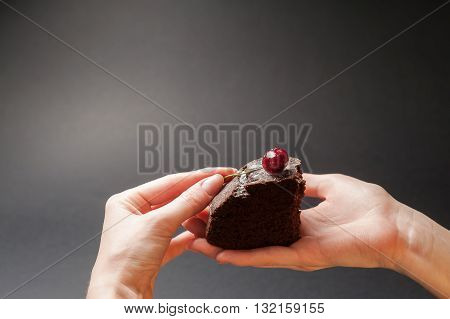 Slice of delicious chocolate cake with cherry on top in a woman hands on a dark background with copy space.