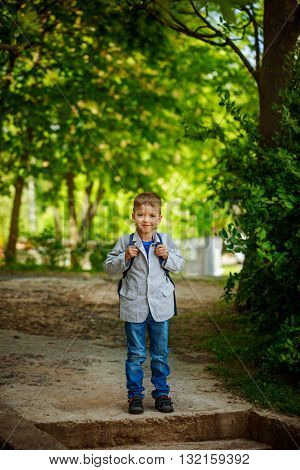 Cute little kid boy with backpack on green nature background. Back to school concept.