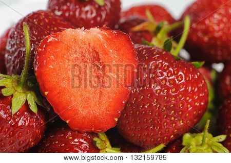 Juicy, tasty strawberry on the glass plate. Strawberries in a glass plate on white background. Close-up fresh strawberries lay on glass plate. Half of strawberry.
