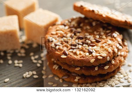 Cookies with sesame and cane sugar pieces on wooden table close-up selective focus