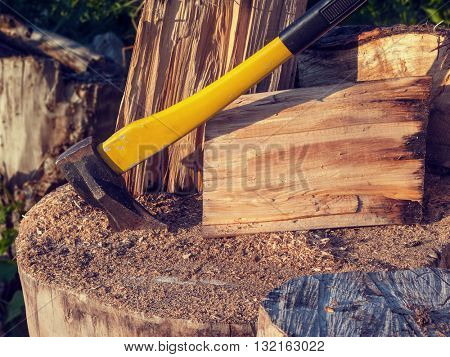 Thematic still life with an ax stuck in a tree and firewood. The texture of the wood, evening lighting.