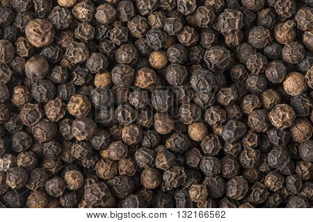 Whole Black peppercorns filling the entire frame.