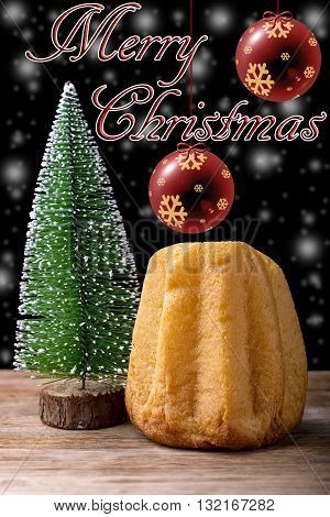 pandoro cake, christmas tree, snow, christmas ball and merry christmas written on wood and black background