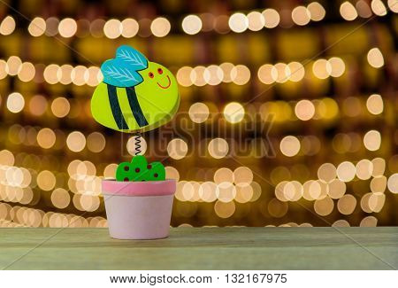 Note clip bee in vase on wooden table with bokeh light background.