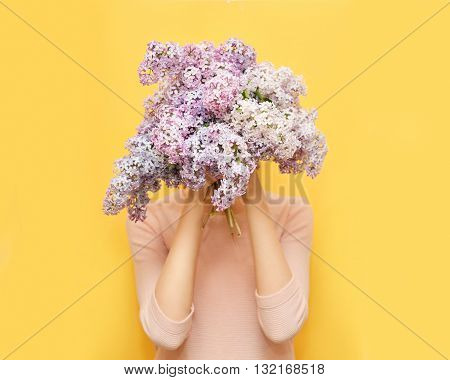 Woman Hiding Her Head In Bouquet Lilac Flowers Over Yellow Background