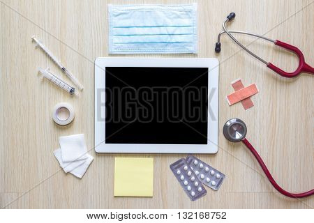 Top view of doctors desk with tablet and medical appliance concept
