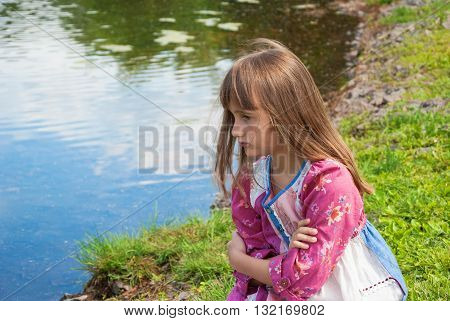 Angry, annoyed Pretty girl on the bank of a pond