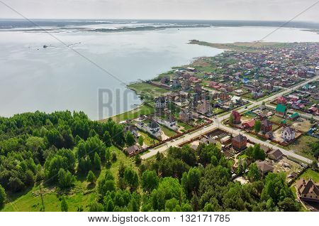 Borovskiy, Russia - May 23, 2016: Bird's eye view onto rural street near Andreevskoe lake and forest. Tyumen region