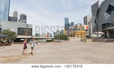 Melbourne - February 23 2016: Young man and woman walking at Federation Square on a hot day near the station Flinders Street Station February 23 2016 Melbourne Australia