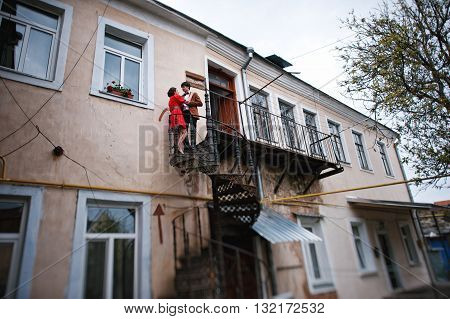 Couple Hugging In Love Background Twisted Staircase To The Balcony. Stylish Man At Velvet Jacket And