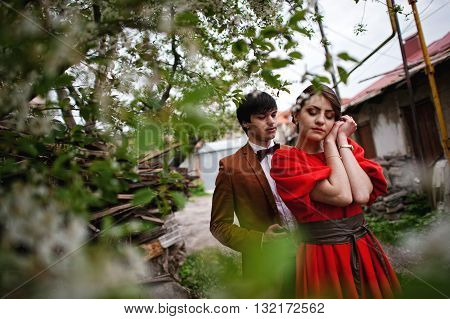 Couple Hugging In Love Near Blooming Trees Garden. Stylish Man At Velvet Jacket And Girl In Red Dres