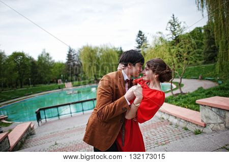 Couple Hugging In Love Near Fountain. Stylish Man At Velvet Jacket And Girl In Red Dress In Love Tog