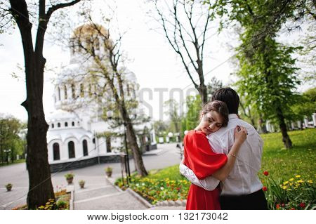 Couple Hugging In Love Background Church. Stylish Man At Velvet Jacket And Girl In Red Dress In Love
