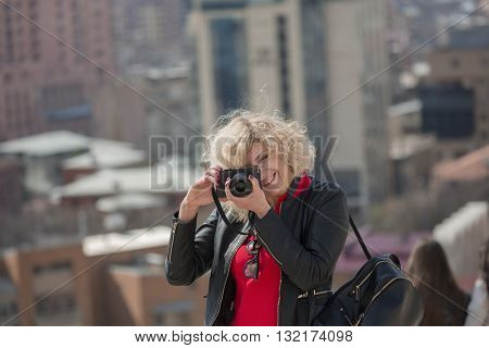 Beautiful blondie woman with curly hair is making photo