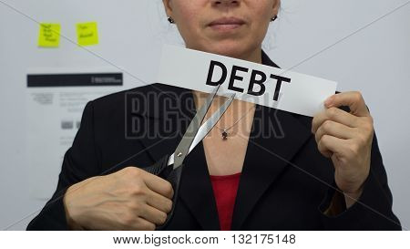 Female office worker or business woman cuts a piece of paper with the word debts on it as a debt reduction business concept.