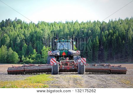 SALO, FINLAND - MAY 27, 2016: Rear view of John Deere 9520T tracked tractor and cultivator on stubble field at spring. The farmer is ready to cultivate the field.
